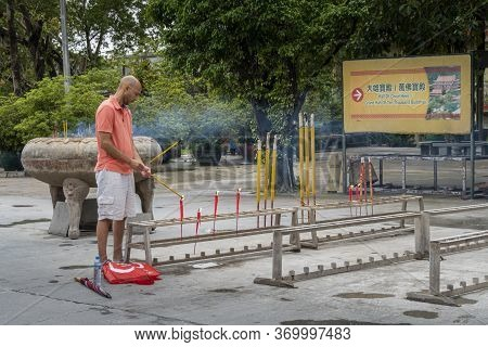 Ngong Ping, Lantau, Hong Kong, May 2018 - A Man Lighting Incense Sticks At Po Lin Monastery, Lantau
