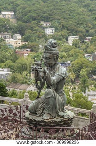 Buddhist Deva Statue Offering Ointment To The Tian Tan Big Buddha  Statue On Lantau Island, Hong Kon