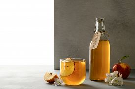 Homemade Fermented Kombucha Or Cider In A Glass With A Slice Of Fresh Apple On A Light Gray Stone Ta