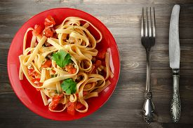 Spaghetti On Red Plate With Fork And Knife Top View. Spaghetti Tomatoes, Onions, Cabbage On Black Wo