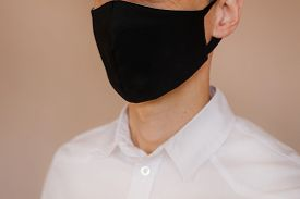 A Man In A White Shirt And Black Protective Mask.