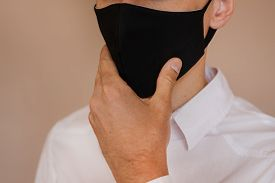 A Man Takes Off His Protective Mask. The End Of The Coronavirus Pandemic.
