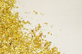 Golden Confetti Scattered On A White Table.