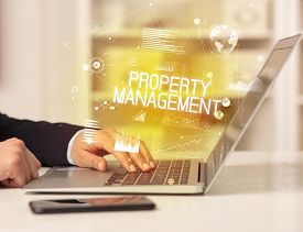 Side view of a business person working on laptop with PROPERTY MANAGEMENT inscription, modern business concept