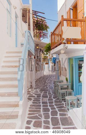 Narrow Street Of Greek Island With Stairs, Flowers And Street Cafe.
