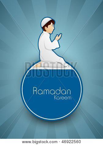 Little Muslim boy in traditional dress praying( reading Namaj, Islamic Prayer) with text Ramadan Kareem on blue background. poster