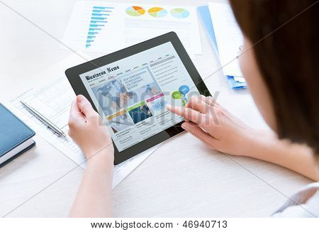 Businesswoman wearing casual shirt sitting at desk and looking latest business news on apple ipad in the office poster