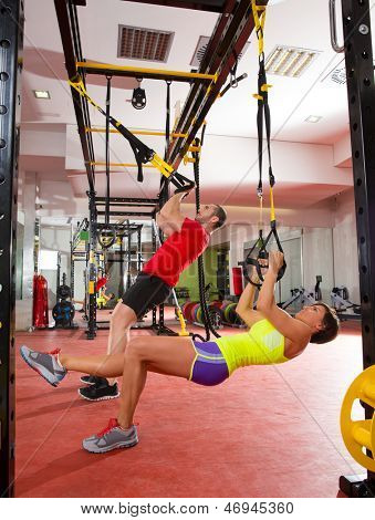 fitness TRX training exercises at gym woman and man push-ups workout