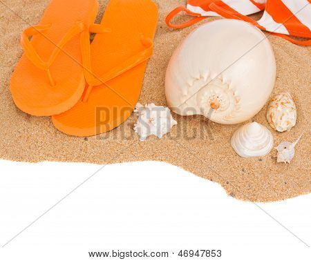 orange sandals and seashells on sand