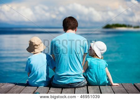 Achteraanzicht van vader en kinderen zitten op houten dok op zoek naar Oceaan