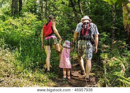 Family On Walk In Mountains In The Summer Day