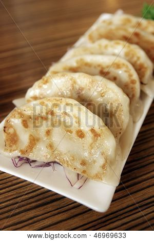 Pot stickers or Jiaozi (Chinese) yaki-gyoza (Japanese) is a Chinese dumpling filled with pork mutton beef chicken fish or shrimp poster