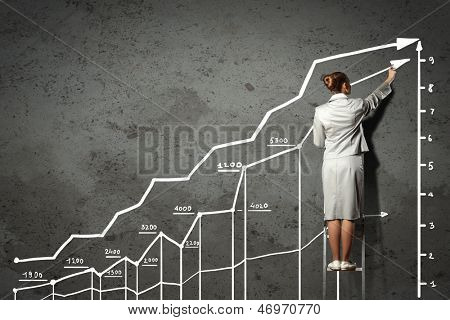 Image of businesswoman standing on ladder and drawing on wall