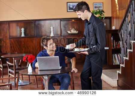 Waiter offering coffee to man with laptop computer in a caf���©