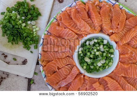 Japanese salmon sashimi dish with green onion leaves poster