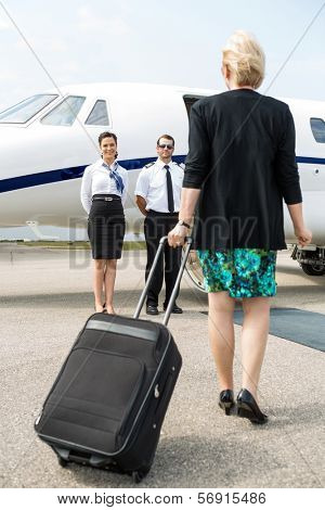 Rear view of businesswoman with luggage walking towards private plane while pilot and airhostess standing by