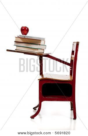 A School Desk With Books, Computer And Apple
