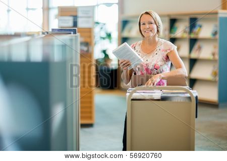 Portrait of smiling female librarian with trolley of books in library