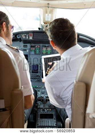 Rear view of pilot and copilot using digital tablet in cockpit of private jet