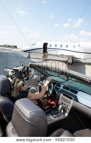 Woman in convertible with private jet in background at airport terminal