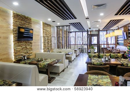 Modern restaurant interior with tables and sofas