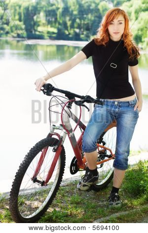 Young Girl With Bicycle Against Blurred Lake