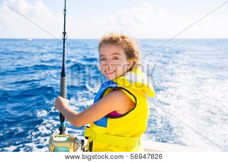 blond  kid girl fishing trolling at boat with rod reel and yellow life jacket