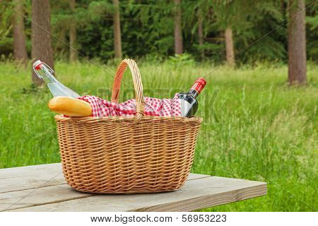 A whicker picnic basket full of food and drink on a table in a woodland setting on a bright summers day.