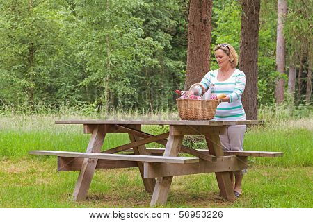 A woman placing a whicker picnic basket full of food and drink on a table in woodland, on a bright summers day.