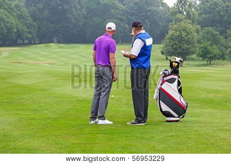 Caddy pointing out a hazard to the golfer on a par 4 fairway