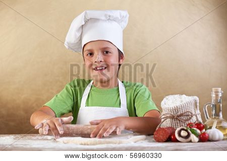 Baker chef boy stretching the dough smeary with flour