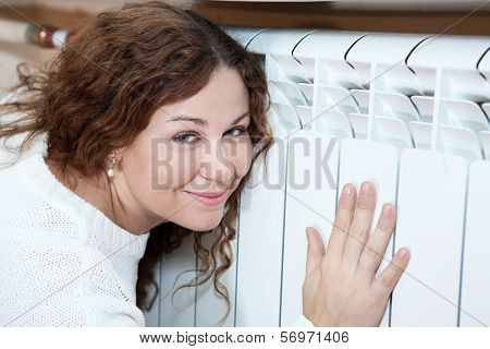Happy Woman Leaning His To Central Heating Radiator