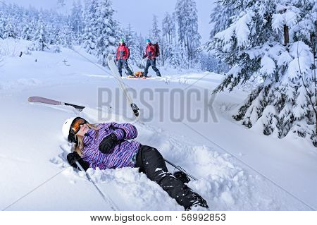 Skier after accident waiting for mountain rescue lying in snow
