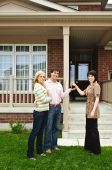 Happy couple getting keys to new house from real estate agent poster
