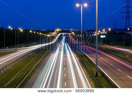 Highway traffic at the evening. Cars lights in motion on the streets. Transport, transportation industry