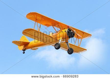 Yellow biplane on the blue sky.