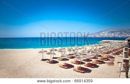 Sunshade umbrellas and deckchairs on the beautiful  Mango beach in Saranda, Albania.