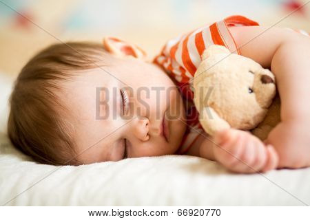 infant baby boy sleeping with plush toy poster