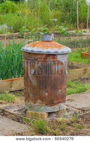 Rusty Garden Incinerator With Plants In Background