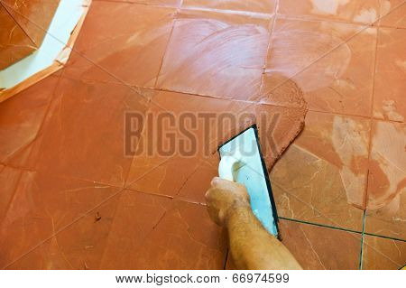 a tiler carries on floor tiles on the grout. grouting of tiles.