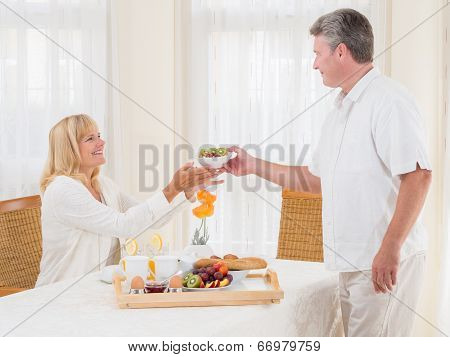 Mature Senior Husband Serving His Wife Healthy Breakfast