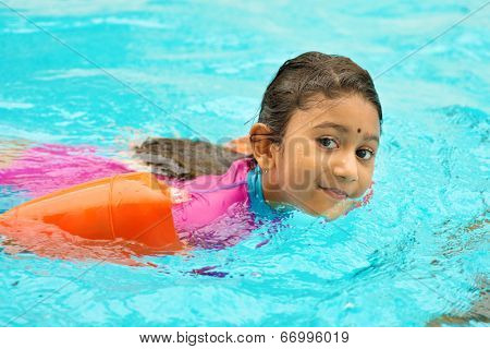Asian girl in swimmer class with float bands. Indian child learning swimming in pool. poster
