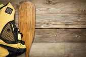 paddling concept - canoe paddle and life jacket against weathered wood with a copy space poster