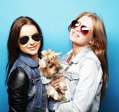 two happy teenage sisters with Yorkshire Terrier poster