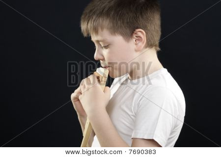 Kid In White Playing Panflute Sideview