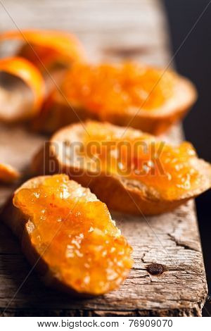 pieces of baguette with orange marmalade closeup on rustic wooden board
