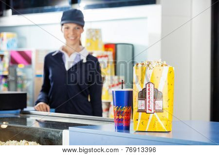 Popcorn paperbag and drink on concession stand at cinema with female worker standing in background