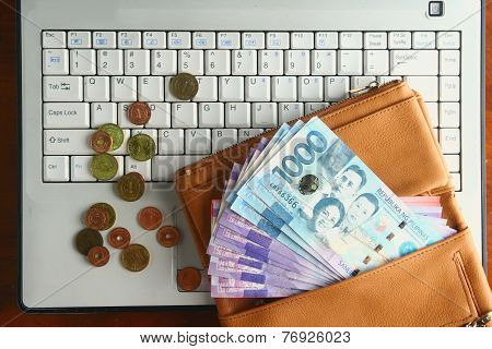 Cash money in a leather wallet and coins on a laptop computer