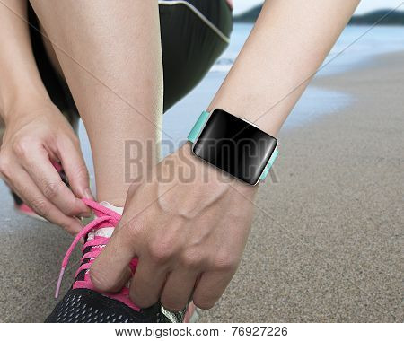 Female Hand Tying Shoelaces Wearing Smartwatch With Bright Blue Watchband