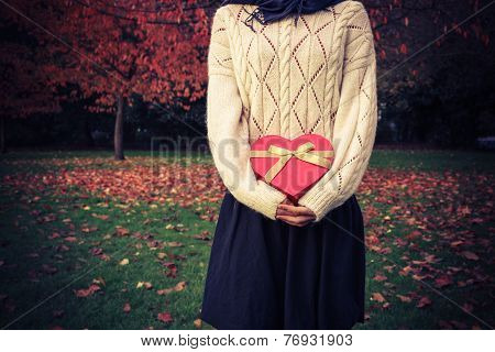 Woman With Heart Shaped Box In Park